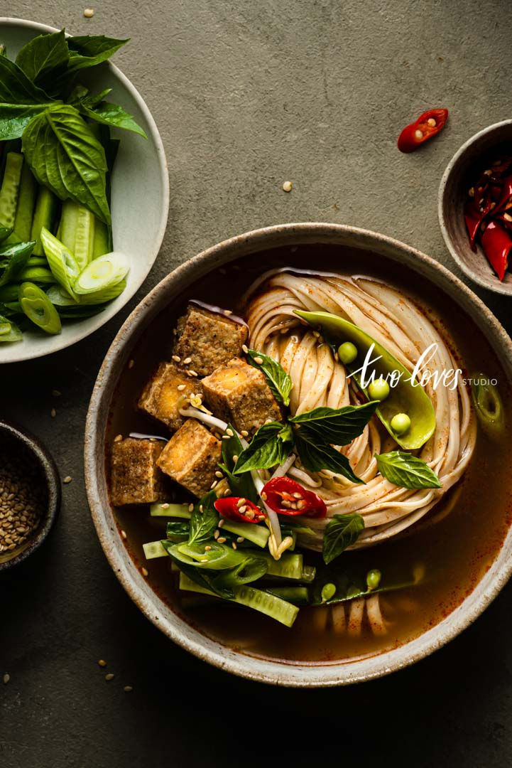 A bowl of Tom Yum Noodle soup with cubed tofu. Showing camera settings for food photography and depth of field.