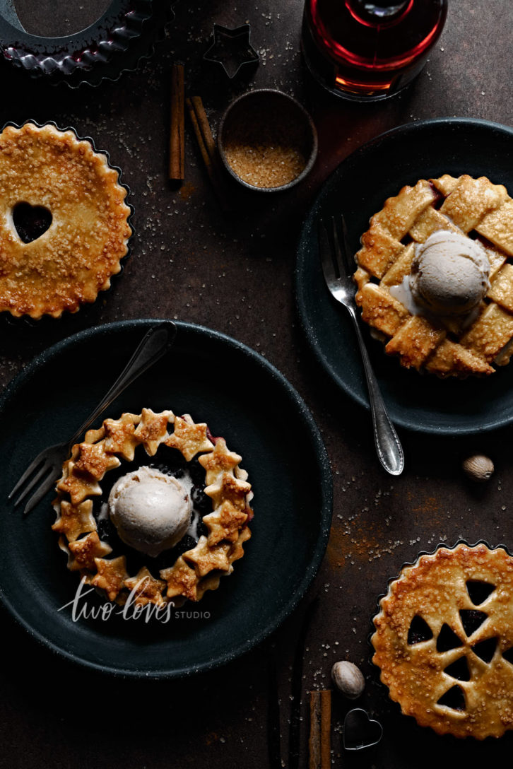 Four mini blackberry pies with caramel ice cream.