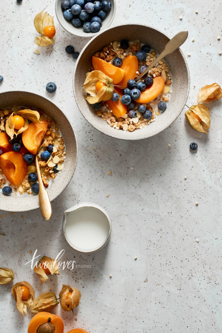 Two bowls of granola with blueberries and sliced apricots with golden spoons.