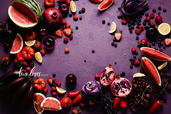 A flat lay of purple, red and yellow fruits on a purple background. Like watermelon, pomegranates, red bananas, strawberries and red grapes. Showing camera settings for food photography and over head flat lays