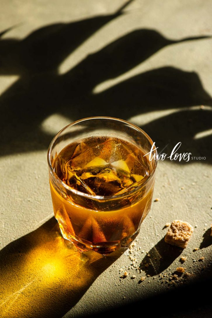 whiskey in a glass with hard lighting and shadow play for natural light food photos.