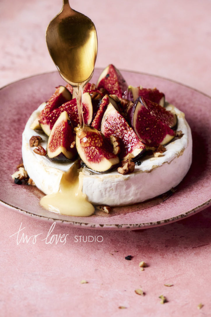 A baked brie with figs and pecans. Drizzled honey is delivered to the top to garnish by a gold spoon. Showing the best camera settings for food photography to freeze motion.