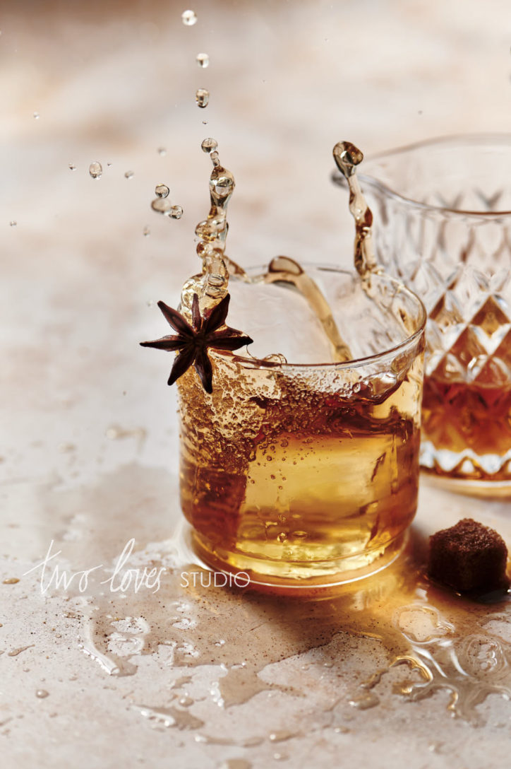 A glass of whiskey with a sugar rim that has an ice cube dropped into it and splashes everywhere. Showing camera settings for food photography and freezing motion.