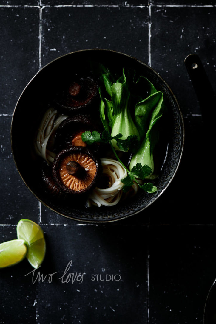 Black background with a black bowl with ramen inside and slices of lime
