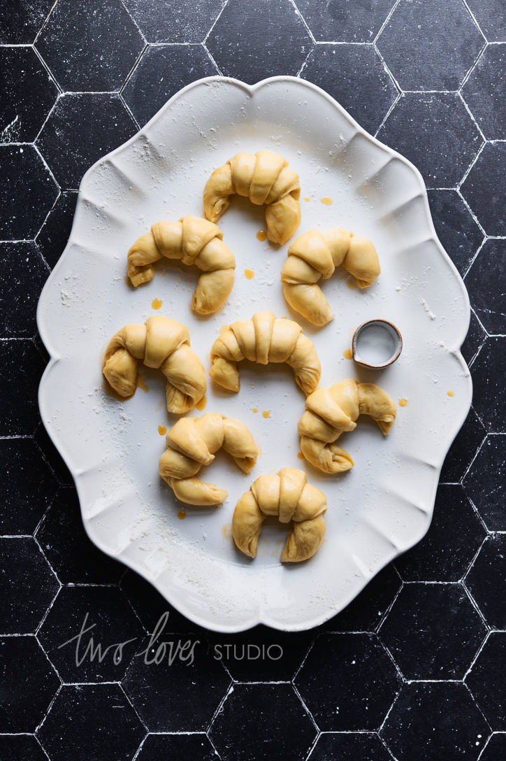 Black background with a white plate and mini croissants and a side jug.