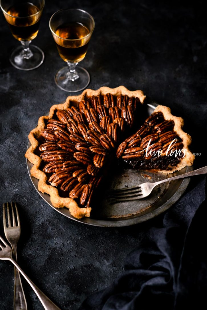 Pecan pie sliced on a dark background.