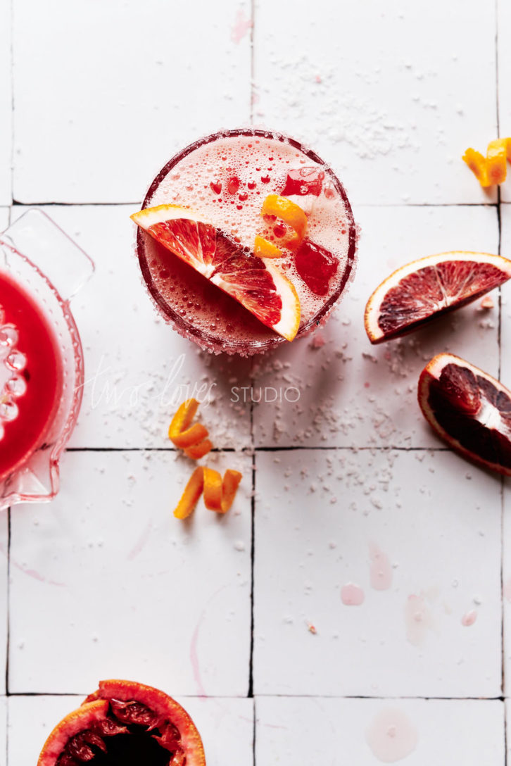 White Moroccan Tile Backdrop with a glass of blood orange margarita and slices of blood oranges.