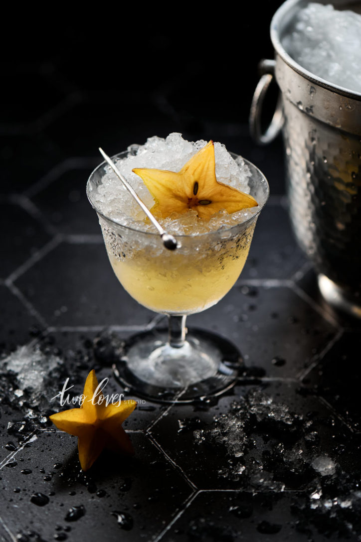 Black Hexagon tile backdrop with crushed ice and  star fruit in a cocktail glass.