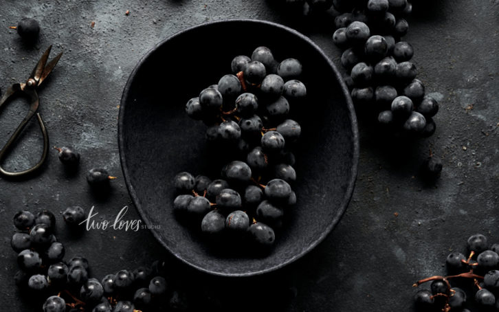 A flatlay of black grapes. A black bowl with black grapes are in the middle.