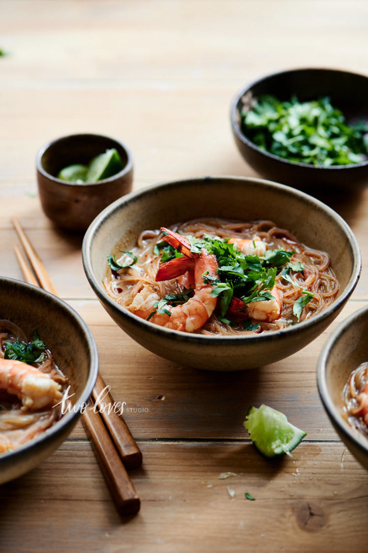 Tom tum soup with prawns and scattered limes.
