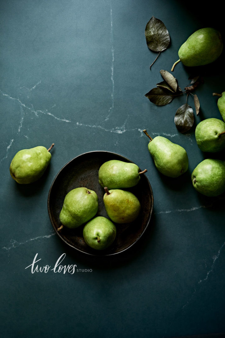 Overhead shot of green pears in a black bowl.