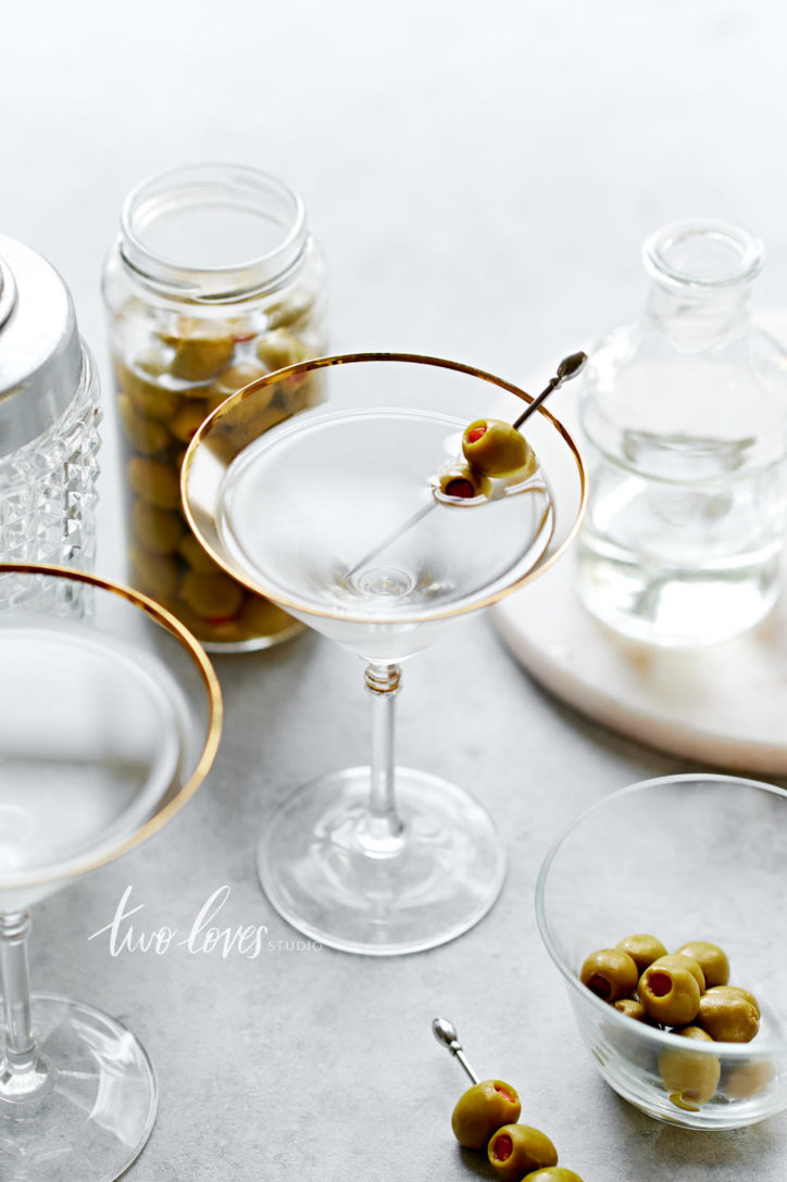 A dirty martini with a two olives on a cocktail pick. With some cocktail making accessories in the foreground and background.