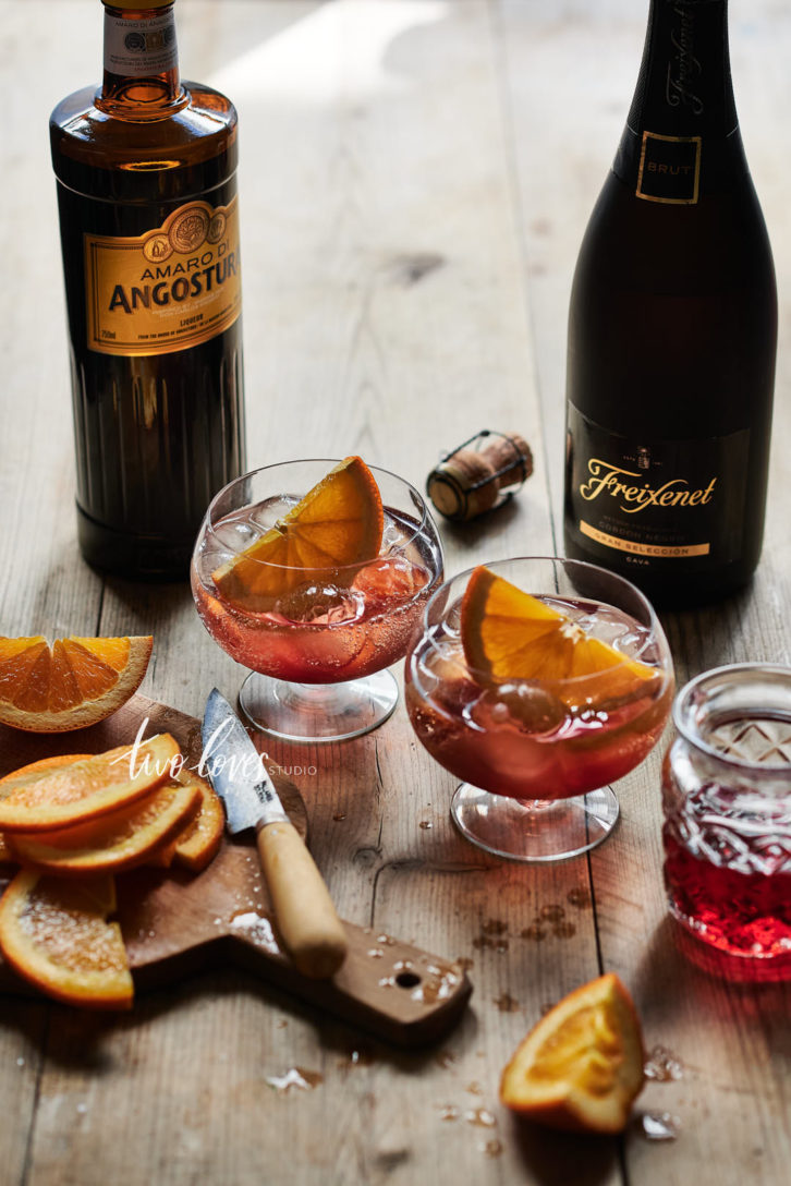 Hibiscus Fizz in two small cocktail glasses with slices of orange.