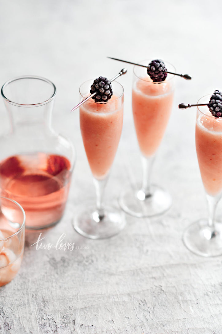 Three tall champagne glasses with frozen rose cocktail drink and blackberry garnishes.