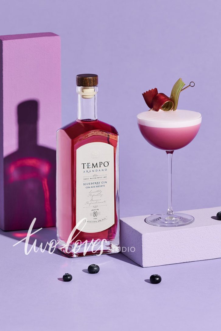 Tempo gin bottle next to a gin cocktail on a purple backdrop.