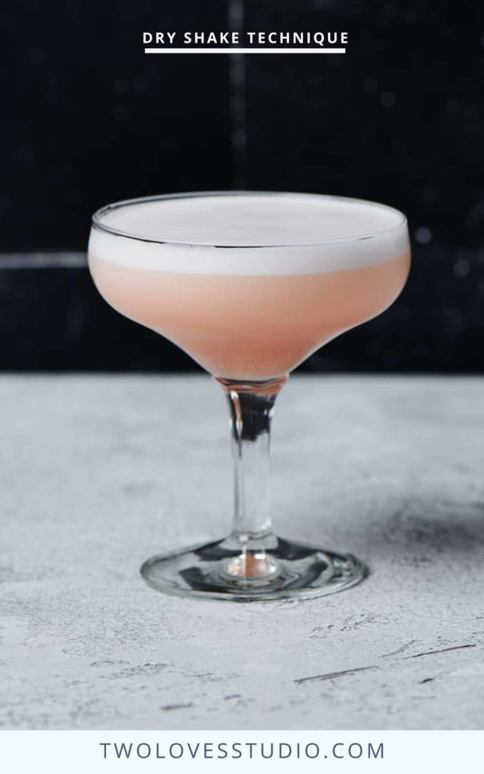 Step by step example. Pink cocktail liquid with a thick dry shake egg foam on top. Sitting on a black backdrop.