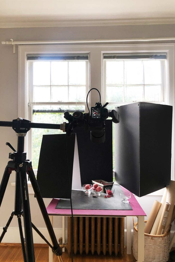 behind the scenes lighting setup for a frozen sorbet shoot. With a camera on a tripod and black foam boards to block light.