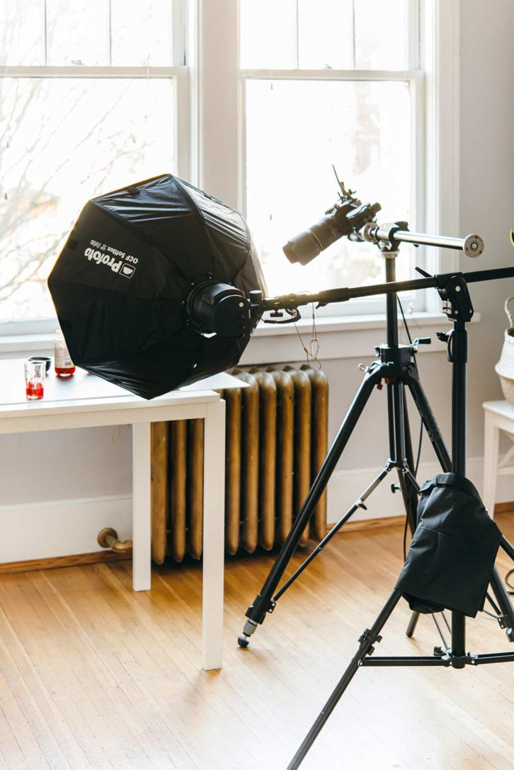 behind the scenes in a food photography studio of a camera on a tripod and artificial light on a lighting stand.