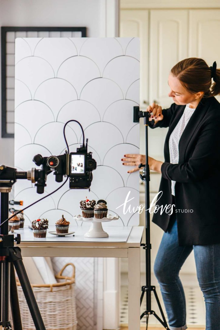 behind the scenes of a cupcake photoshoot with a background and the food photography equipment to capture the shot.
