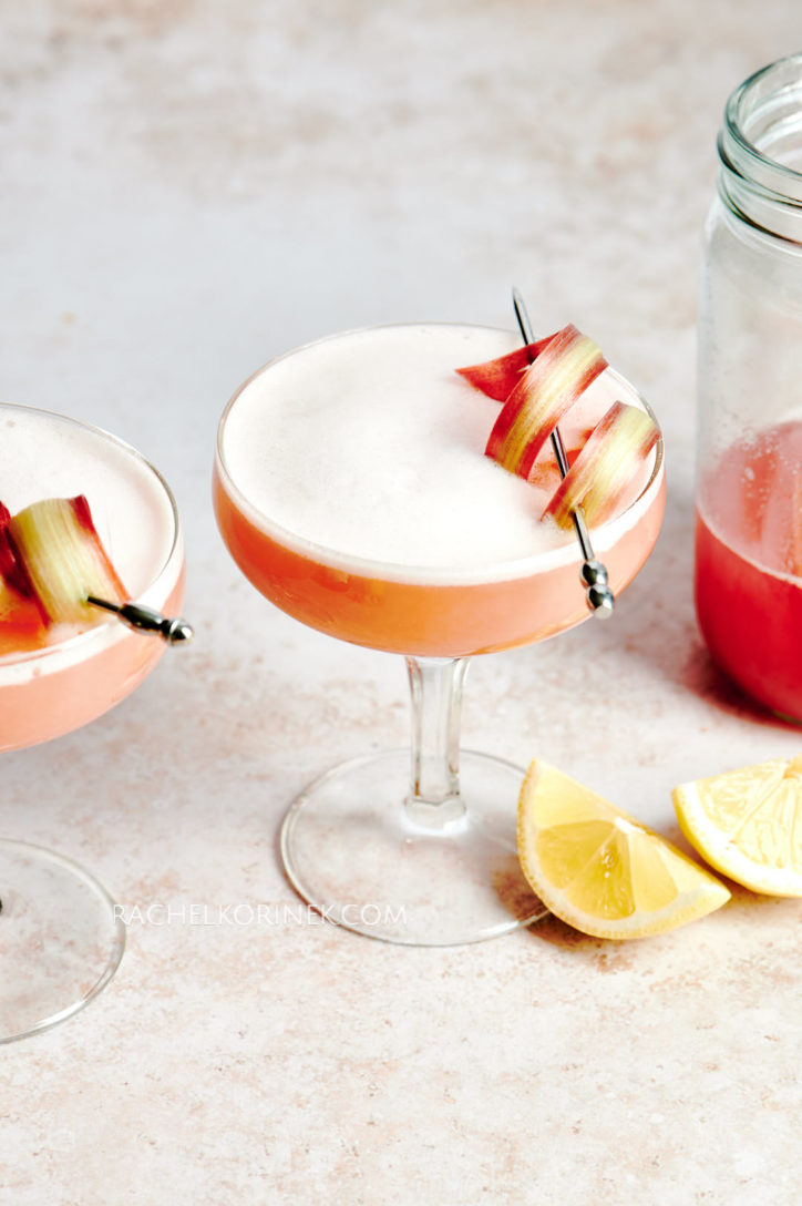 Two peach dry shake cocktails with a swirled garnish on the top and a wedge of lemon.