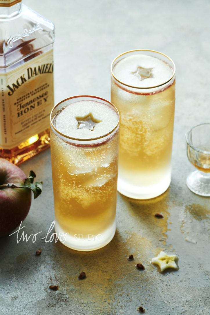 Jack Daniel cocktails on a grey backdrop in two tall glasses with apple circle garnishes.