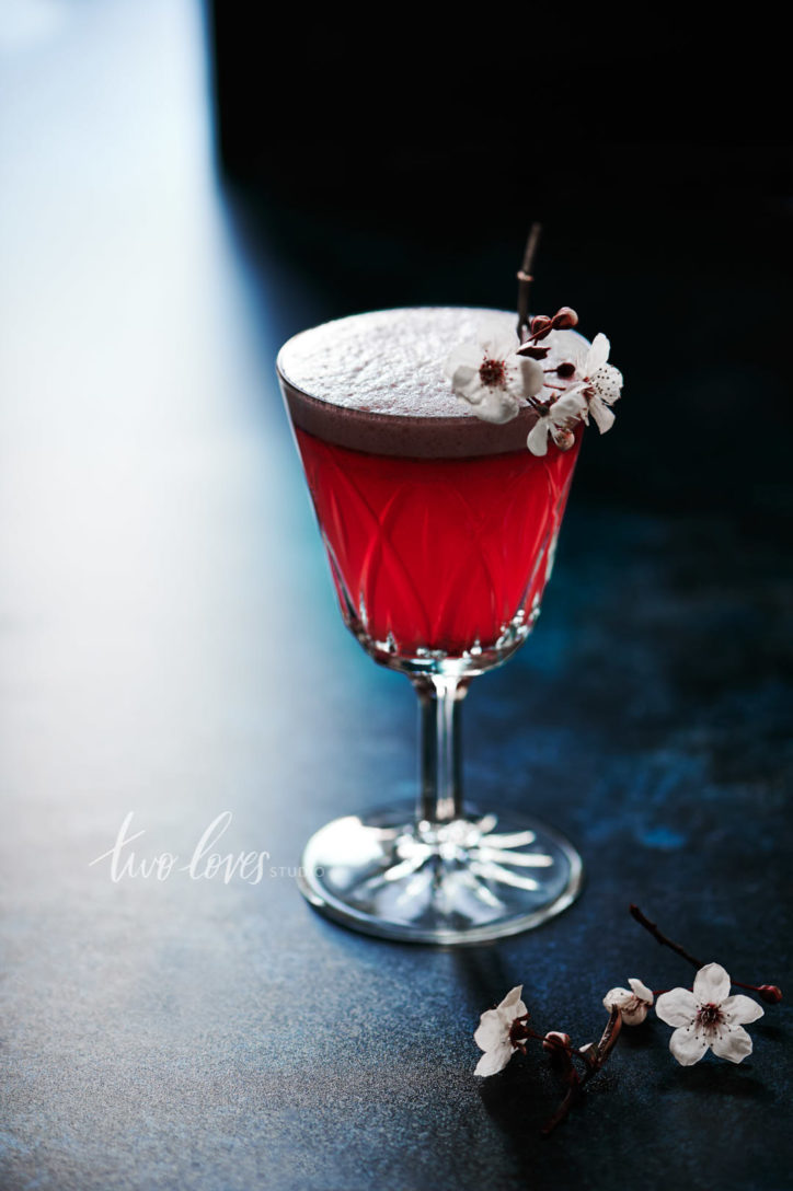 Single cocktail with a cherry blossom cocktail garnish on a dark blue background.