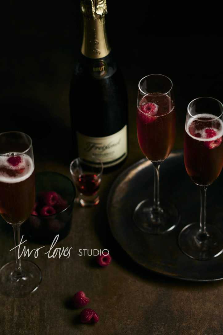 A wooden table with three champagne cocktails and raspberries garnishes.