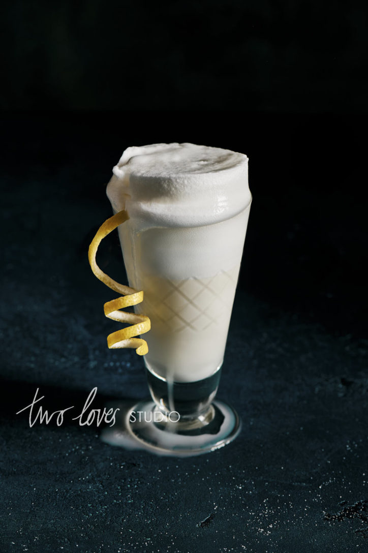 Thick and creamy cocktail drink photo with a foam topper and a lemon twirl garnish.