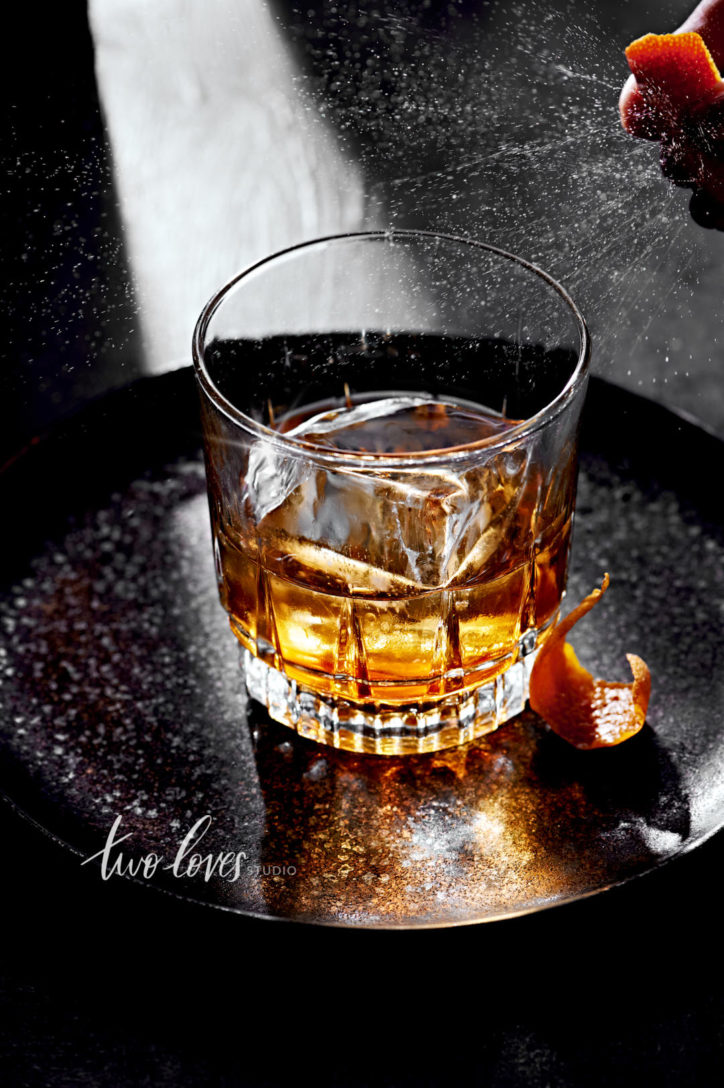Drink Photo of a whiskey in a rocks glass on a black plate with an orange garnish.