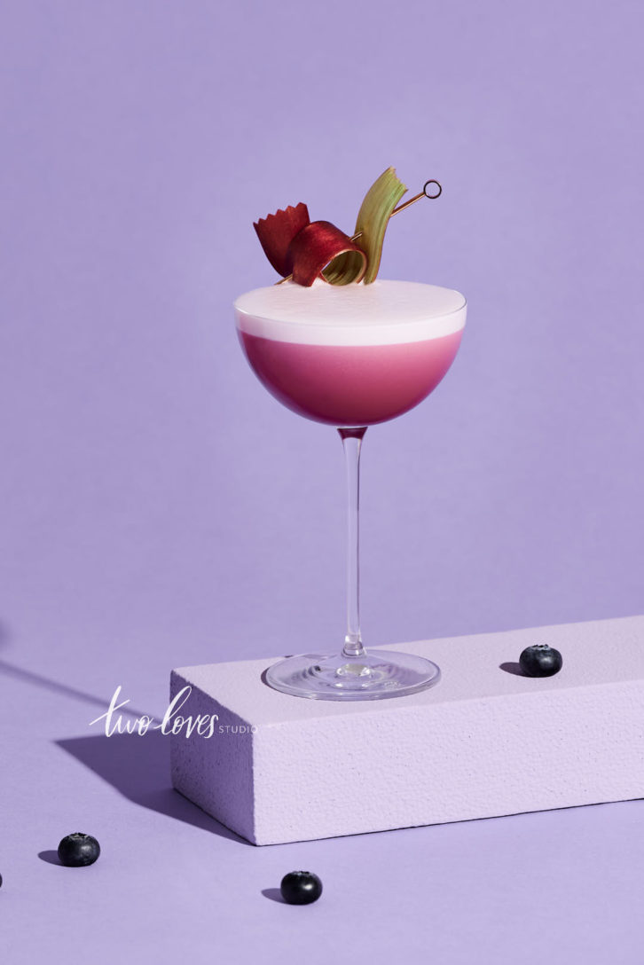 A stunning pink cocktail with a thick dry shake foam on top with a purple backdrop, resting on a stand with berries around it and a fancy garnish.