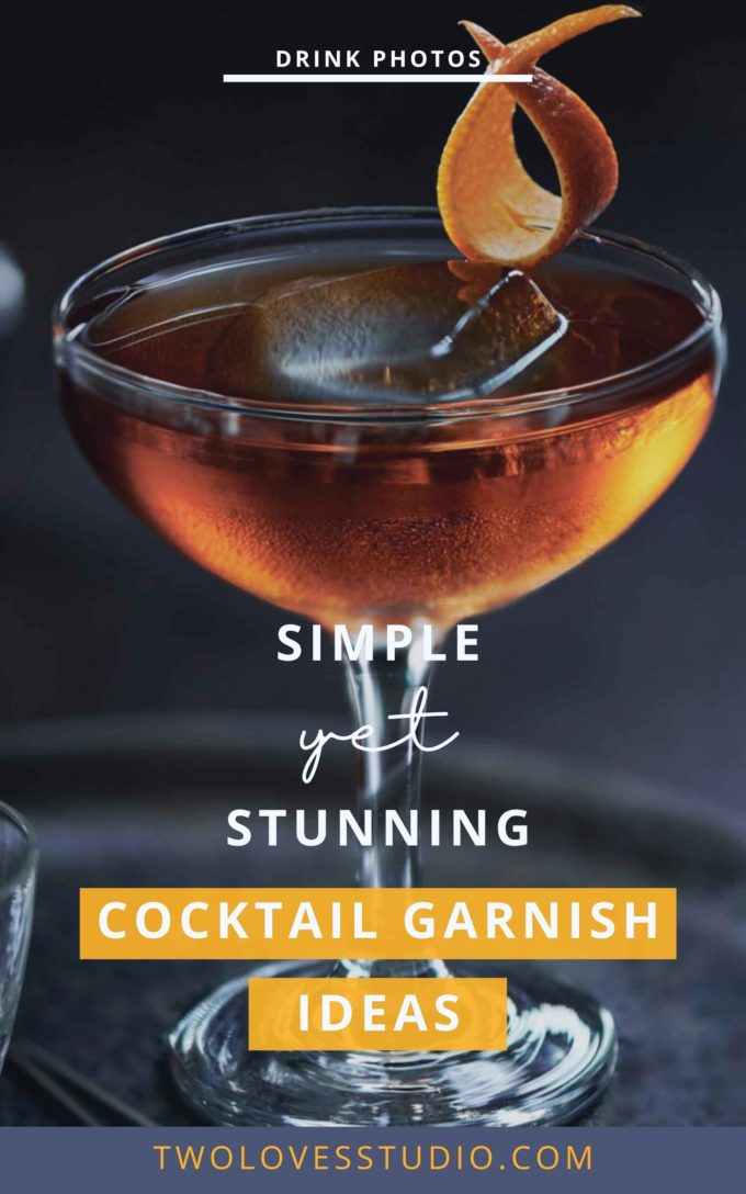 A simple orange ribbon cocktail garnish on the rim of a cocktail on a dark back ground.