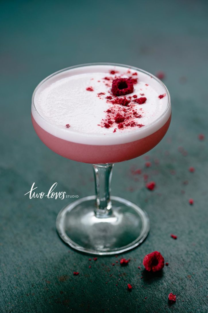 Freeze dried Raspberries sprinkled on top of an egg white foam cocktail.