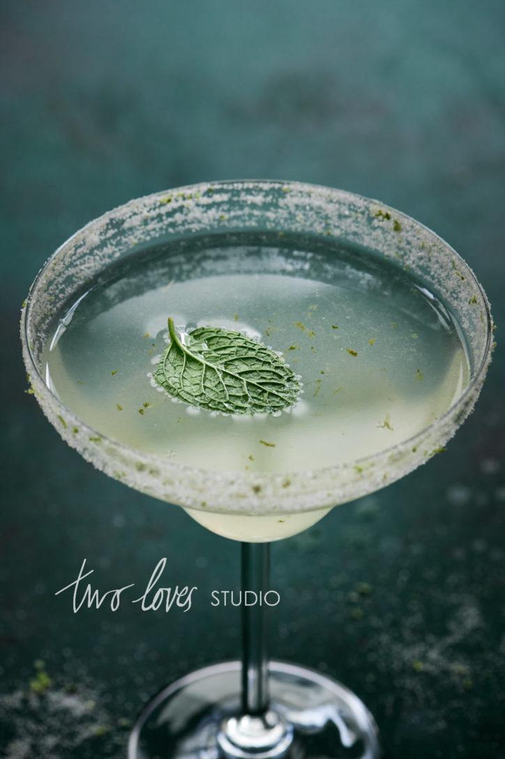 Margarita cocktail on a dark green backdrop with a mint leaf garnish.