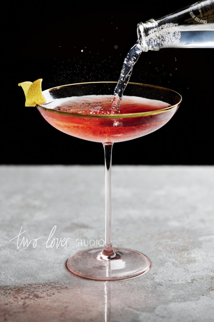 Cosmopolitan cocktail with a lemon wedge and sparking water being poured in from the top right.